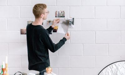 A man displaying fashion sketches on the wall