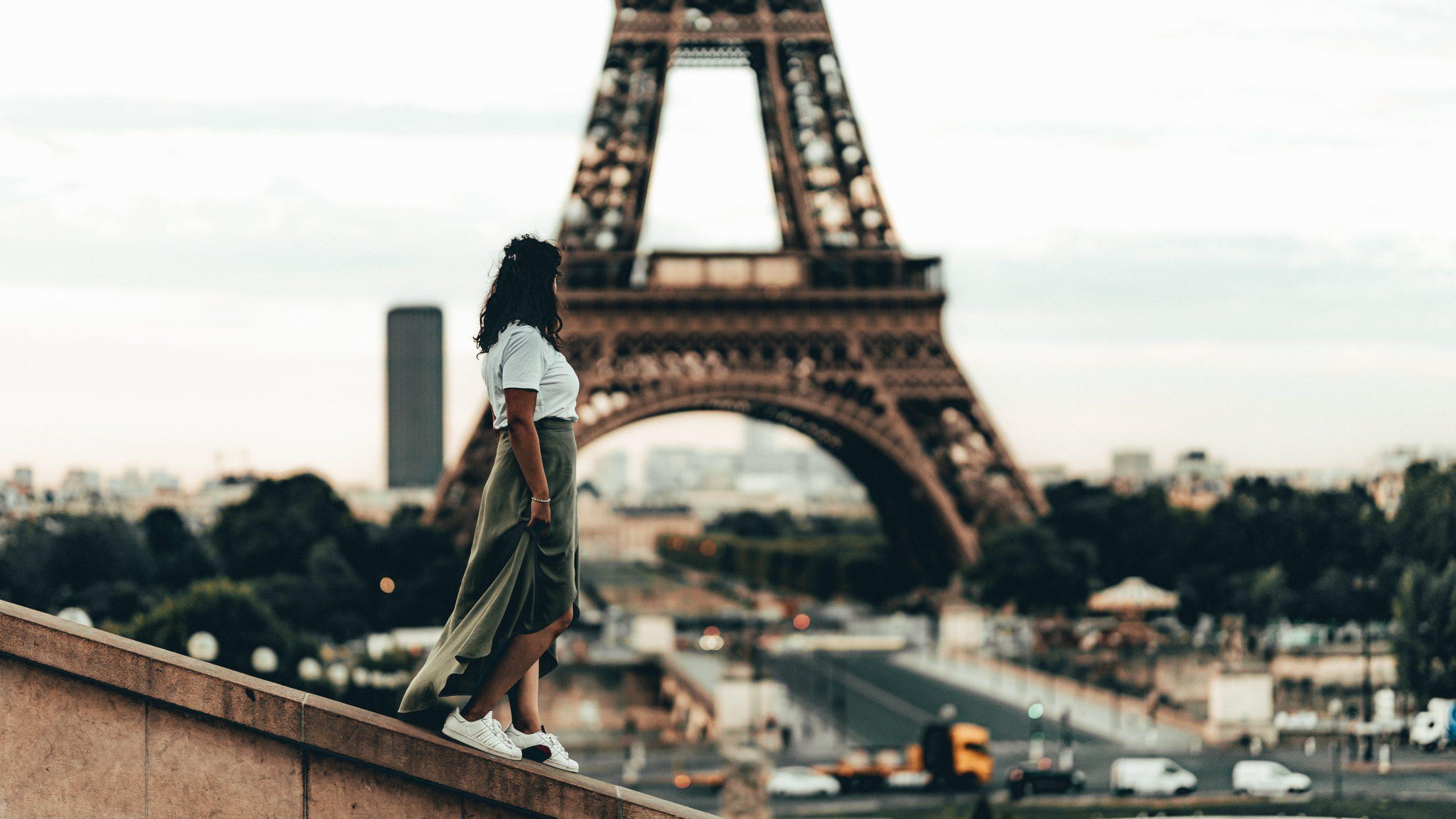 woman walk past the Eiffel Tower in Paris