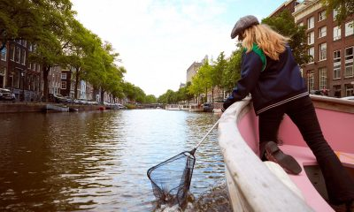 Woman fishing plastic bottles in Amsterdam