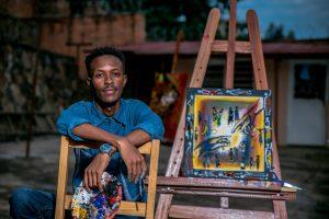 Artist posing near a painting
