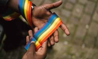 Employee holds a rainbow ribbon