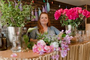 Florist owner of a small business posing with flowers
