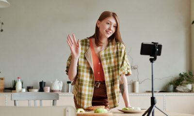 A female content creator recording a video in her kitchen