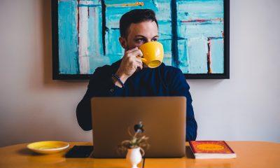 Young man drinking coffee in a yellow mug