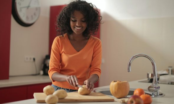 Woman cutting potatoes in the kitchen